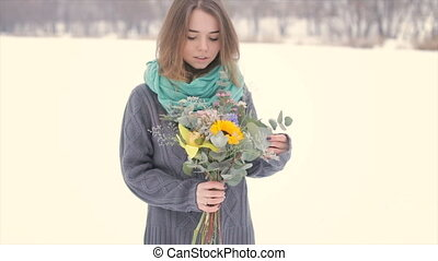 A girl without winter clothes with a bouquet of flowers in her hands