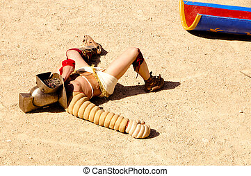 gladiator - a gladiator lying on the arena of a amphitheater