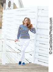 A Glamorous pretty young hipster woman in summer white t-shirt in sneakers in trendy jeans in stylish sunglasses is standing near a wooden wall in the city. European girl on a walk on a sunny summer day
