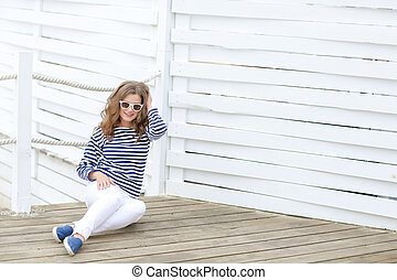 A Glamorous pretty young hipster woman in summer white t-shirt in sneakers in trendy jeans in stylish sunglasses is standing near a wooden wall in the city.