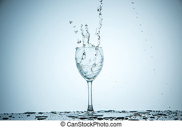 A glass being filled with water on white background