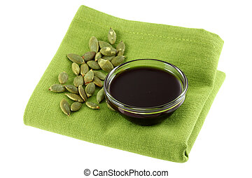 Pumpkin Seed Oil - A Glass bowl of Pumpkin Seed Oil and some...