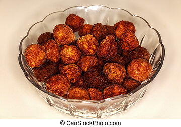 a glass bowl with fried meatballs