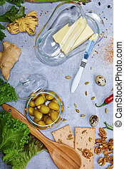 A glass container for butter next to a glass bowl of green stuffed olives on a gray background. Butter knife, a wooden spoon.