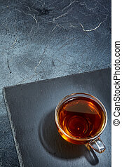 A glass cup of black tea on a dark greyish marble background...