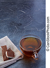 A glass cup of black tea with chocolate on a dark greyish ...