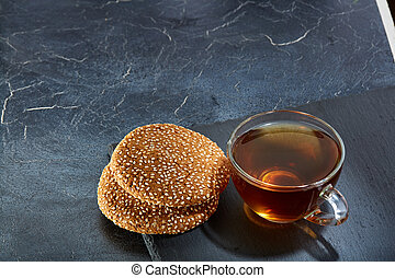 A glass cup of black tea with cookies on a dark greyish marble background, shallow depth of field. Breakfast background