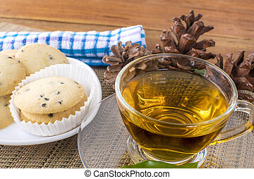 A glass cup of black tea with cookies on a dark greyish ...