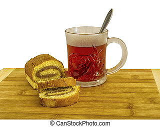 A glass cup with tea and biscuit roulade