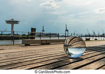 glass globe lies on a bech in Hamburg harbour