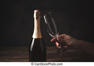 A glass in a woman's hand next to a closed bottle of champagne on a dark wooden background.