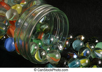 spilled marbles - A glass jar of spilled marbles.