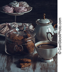 A Glass jar with cookies and a cup on a wooden table on dark background. Vintage Style