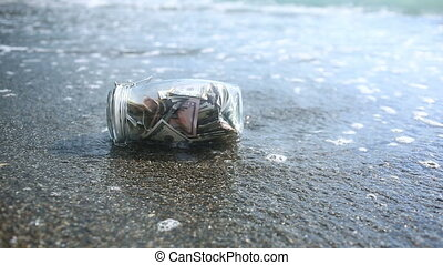 A glass jar with paper money dollars against a sea waves background. Accumulate the savings on leave by the sea or the ocean. beach.