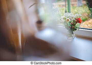 A glass jug with flowers in it stands on a white window sill, and outside the window you can see the home garden.