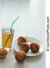A glass of Apple grapefruit juice, three muffins on a plate and more sweet muffins .Fresh breakfast on the morning.
