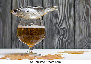 A glass of beer and dried maple leaves. There is a roach on the glass.