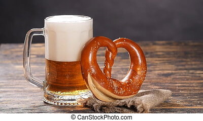 A glass of beer and pretzel on a wooden table - A glass of...