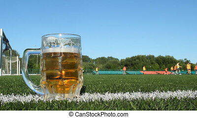 A glass of beer is on a football field, football is played in the stadium