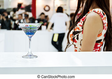 A glass of Blue Laguna cocktail with a sexy girl on background