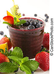 a glass of blueberry smoothie surrounded by fresh fruits