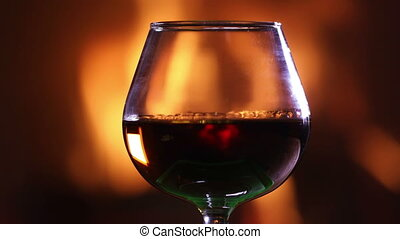 A glass of brandy against the burning fireplace