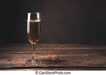 A glass of champagne and a bottle stopper on a wood background.