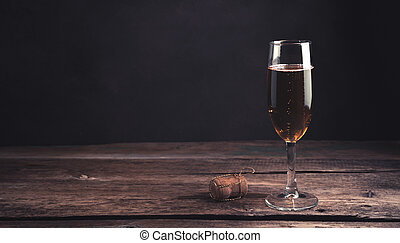 A glass of champagne on a dark wooden background.