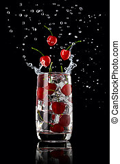 A glass of cherry lemonade with ice, splashing in different directions and three cherry berries falling into the glass, on a black background