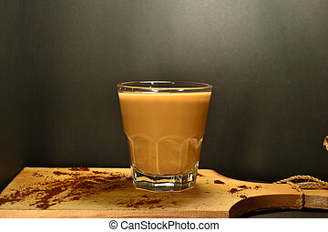 a glass of coffee milk on a black background