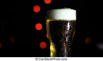 A glass of cold beer on a black background with colored lights. Drops of water flow down the glass. Mood of the holiday. HD
