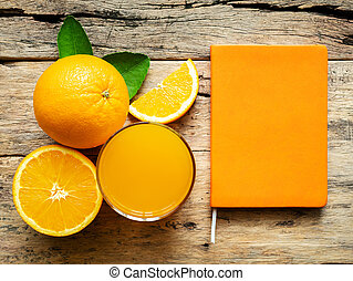 a glass of fresh orange juice and group of fresh orange fruits with green leaves, on wooden background with orange cover book color. vitamin C and fruit product display or montage, studio shot