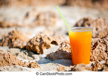A glass of juice on the beach