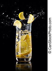 A glass of lemon lemonade with ice, splashing in different directions and three slices of lemon falling into the glass, on a black background