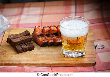 A glass of light beer with smoked fish and black fried bread in garlic. Beer and beer snack on a wooden Board.