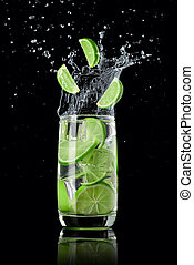 A glass of lime lemonade with ice, splashing in different directions and three slices of lime falling into the glass, on a black background