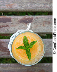 A glass of melon smoothie decorated by fresh peppermint...