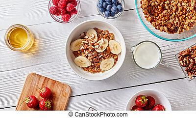 A glass of milk, juicy different berries, honey and a plate with granola and banana slices on a white wooden table. Healthy breakfast. Top view