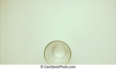A glass of milk with straws and two glazed donuts. Stop motion, animation, top view