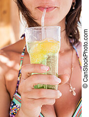 A glass of mojito with lemon and ice in the hands of women