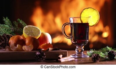 A glass of mulled wine (gluhwein) and a plate of fruit on...