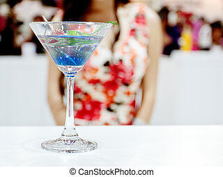 A glass of Ole cocktail with a sexy girl on background