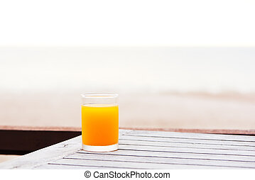 A glass of orange juice on wooden table