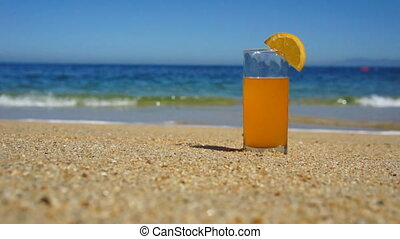 Orange Juice - A glass of Orange Juice standing in the sand.