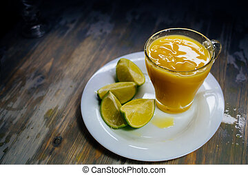 A glass of orange juice With a big splash and lime on a plate