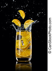 A glass of orange lemonade with ice, splashing in different directions and three orange slices falling into the glass, on a black background