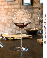 A glass of red vintage wine stands on wooden chest