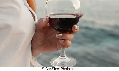 glass of red wine in the hands of a woman against the sea