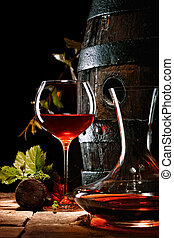 A glass of red wine next to a decanter with an oak cask in ...