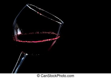 a glass of red wine on black background